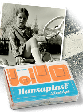 1969: six-year-old girl on go-kart in the late sixties, historic Hansaplast plaster package with strips, strip of asphalt.