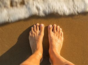 Naked feet standing on the beach with a wave coming in