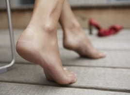 Naked feet walking on a wooden floor towards red high heels