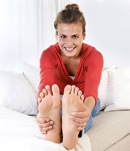 Close-up of girl holding feet