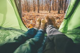 Two people in hiking boots lying in a green tent in the woods