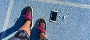 Sport shoes on blue ground next to a cellphone with headphones.