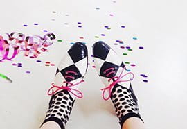 Black white patterned shoes lying on the floor with confetti