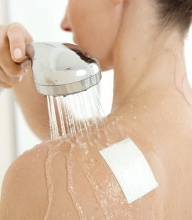 Woman showering with plaster on her shoulder